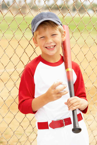 Smiling youth baseball player in a red and white uniform holding a wood baseball bat.