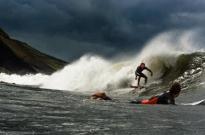 supporting another surfer catching a wave in scotland community sport for mental health eco clothing brand in outdoors big left hand wave