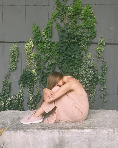 Woman in pale pink outfit covering face with hair and sitting in front of a wall covered in English ivy leaves, for Ivy Leaf Skincare