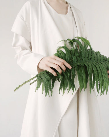 A woman in white holding a bundle of green leaves, for Ivy Leaf Skincare