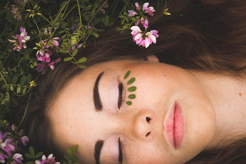 Woman laying with green field with pink flowers, for Ivy Leaf Skincare blog