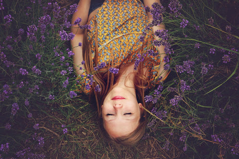 Woman laying upside down in dark field with eyes closed, for Ivy Leaf Skincare