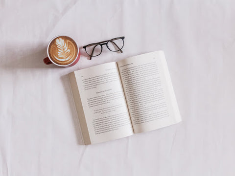 An open book, a pair of reading glasses and a latte on a bed spread, for Ivy Leaf Skincare blog