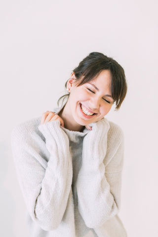Woman holding onto turtleneck smiling widely with eyes closed, for Ivy Leaf Skincare