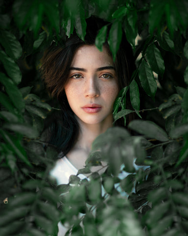 Woman standing behind dark leaves, for Ivy Leaf Skincare