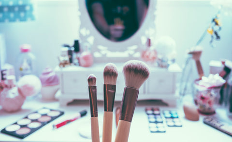 3 makeup brushes held in front of beauty vanity, for Ivy Leaf Skincare blog