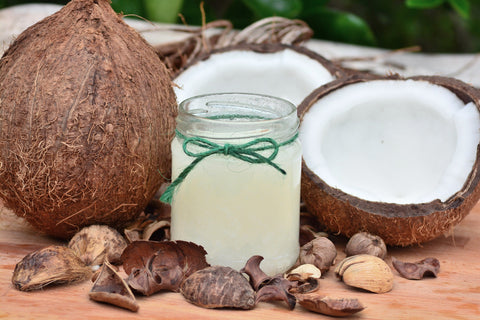Jar of coconut oil on table top with sliced open coconuts, for Ivy Leaf Skincare blog