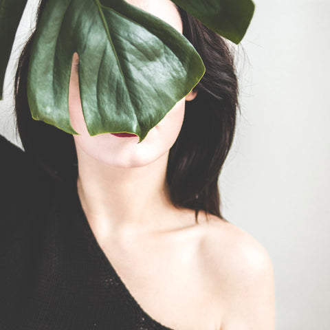 Woman standing behind dark green leaf for Ivy Leaf Skincare, covering face