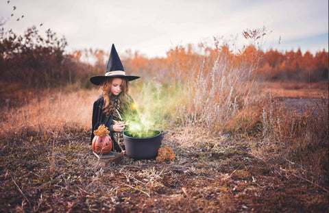 Child dressed as witch, lighting cauldron in the middle of a field, for Ivy Leaf Skincare blog