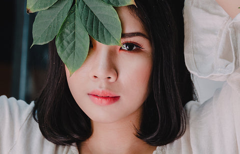 Woman covering one eye with plant leaves, for Ivy Leaf Skincare