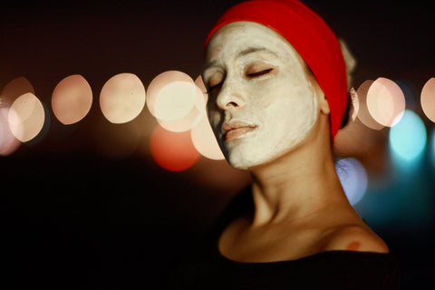 Woman with cream face mask applied, outside in city light lit night sky, for Ivy Leaf Skincare