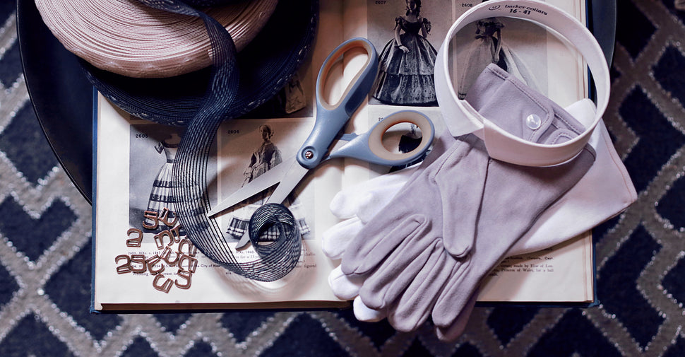Men's cotton gloves, detachable collar, silicone elastic, and quick rig shoe hooks scattered on historic dress-making guide