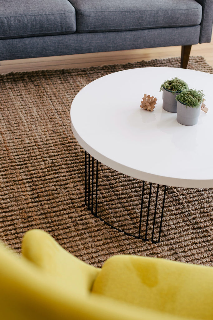 modern white coffee table on metal legs, next to yellow armchair and dark grey sofa made of fabric