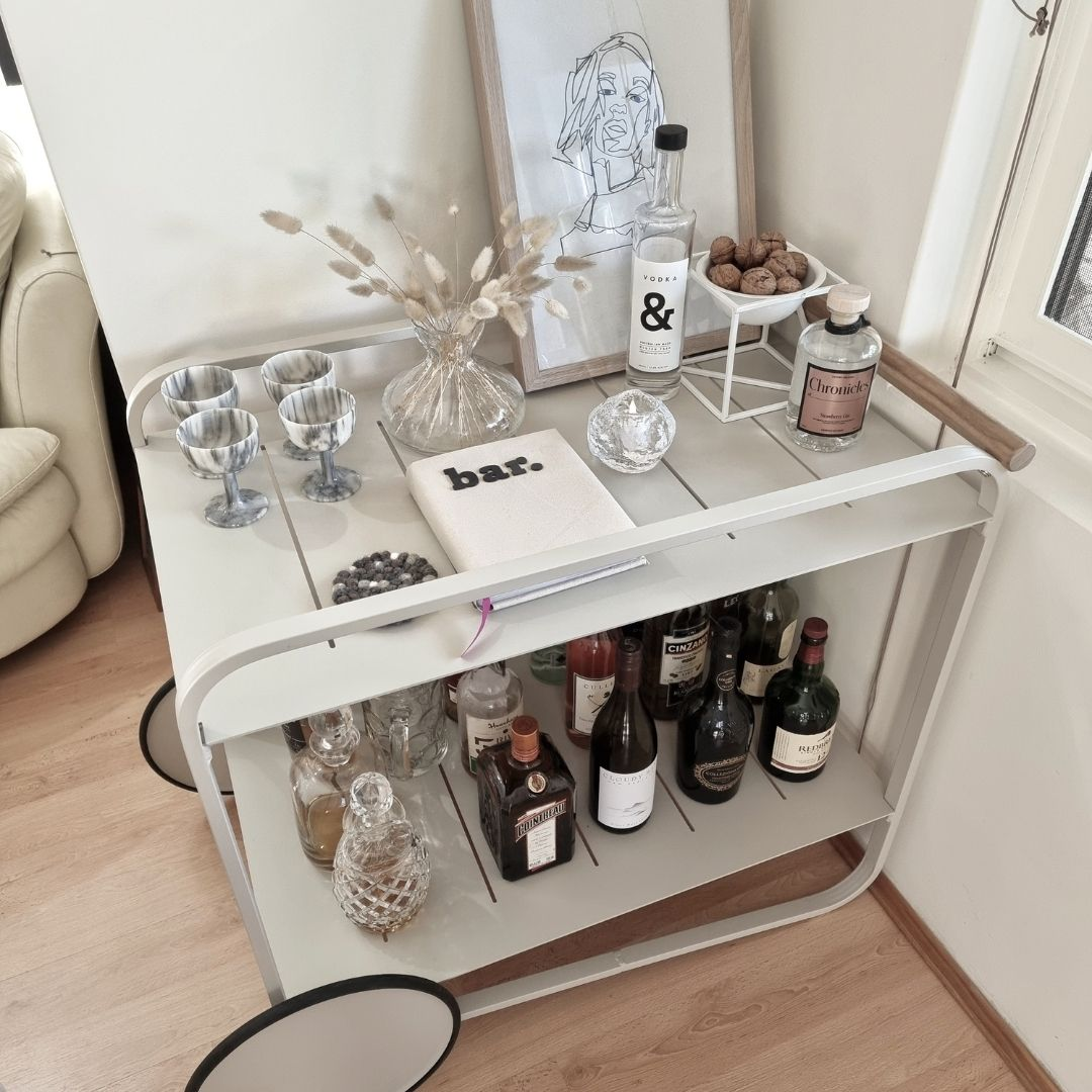 Indoor bar cart with glasses and display items on the top shelf and bottles and decanters on the bottom shelf
