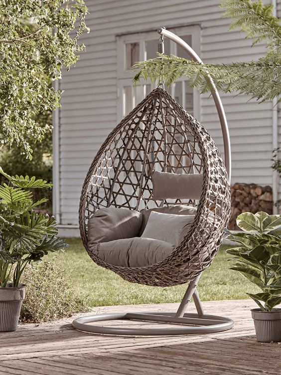beige hanging egg chair with beige cushions in the garden