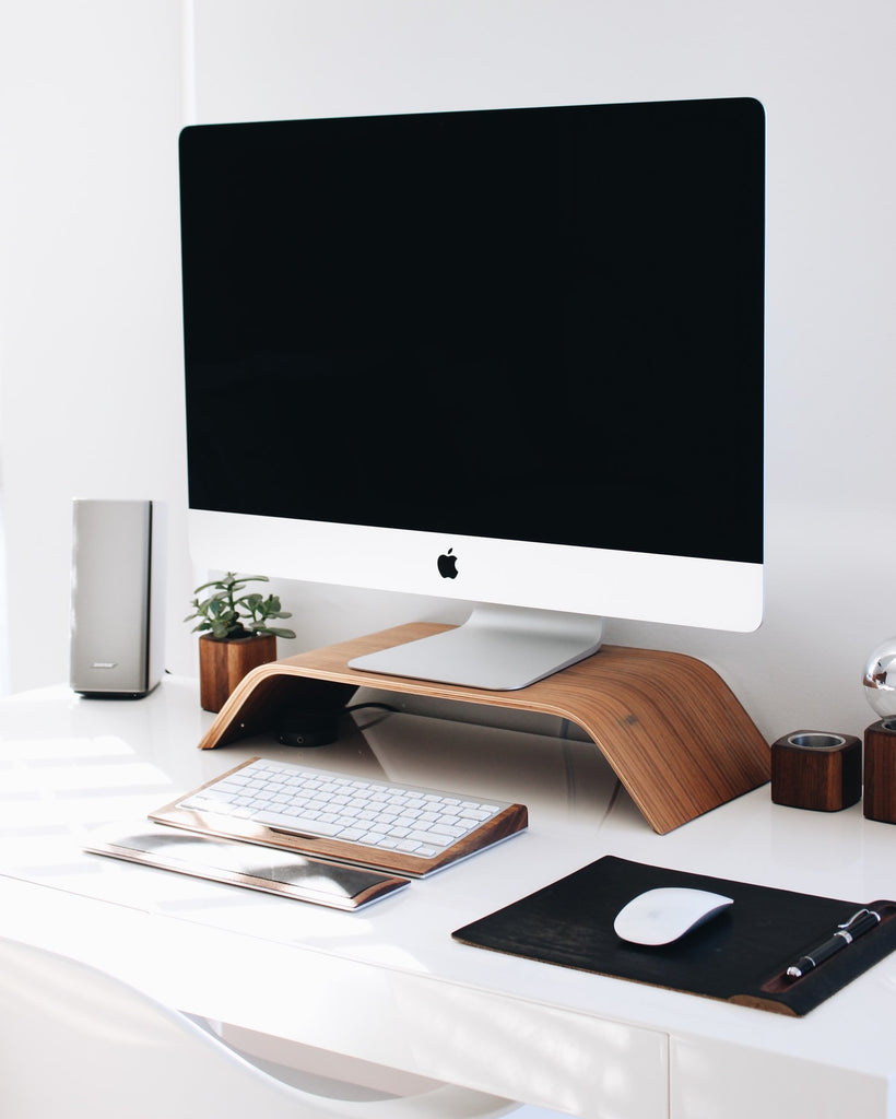 a white desk with a wooden stand on it, a mac monitor, a mouse, a keyboard and a speaker. Everything is arranged in warmer tones, white, brown and silver colors.