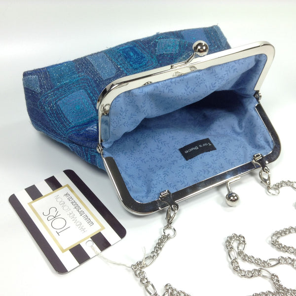 Blue cotton lining and chain strap of denim clutch or shoulder frame purse bag