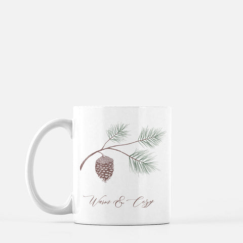 White ceramic mug with evergreen and pinecone drawing with the words Warm & Cozy