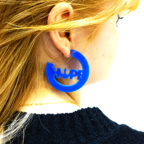 Model wears démocrat blue Hope earrings with the Rebel Alliance sign from Star Wars