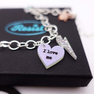 Close up of I love me charm necklace choker with star and lightning bolt charms
