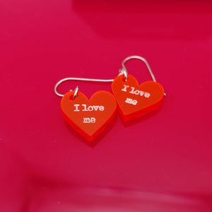 I love me loveheart earrings shown on red