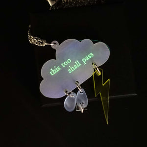 This too shall pass raincloud necklace with frosted and iridescent rain drops and lightning blolt. Words etched in glow in the dark paint.