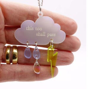 This too shall pass necklace with hand behind for scale.