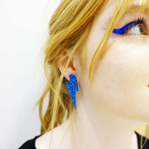 model wears large blue glitter lightning bolt studs