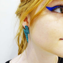 Load image into Gallery viewer, model wears large teal glitter lightning bolt studs