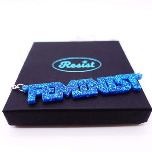 blue glitter all caps feminist necklace on box