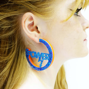 model wears hot glitter blue Mary Beard Women & Power earrings, statement hoops