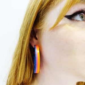 model wears hot glitter blue Mary Beard Women & Power earrings, statement hoops showing the bands of colour