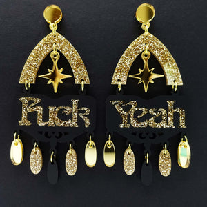 Fuck yeah earrings in black and gold glitter shown hanging on black background