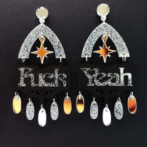 Fuck yeah earrings in black and iridescent silver glitter shown hanging on black background]