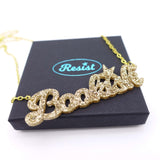 gold glitter bookish necklace on box