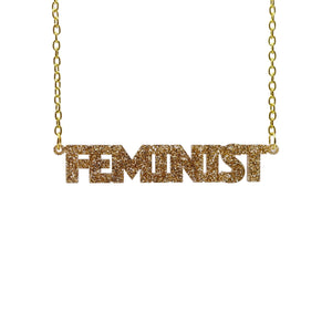 gold glitter all caps feminist necklace hanging