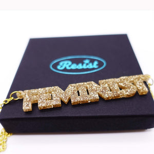 gold glitter all caps feminist necklace on box