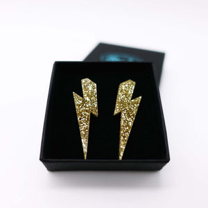gold glitter medium lightning bolt stud earrings shown in box