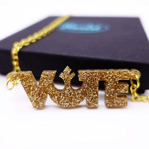 close up of gold glitter Rebel Alliance vote necklace