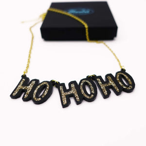 close up of gold HO HO HO Christmas necklace