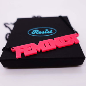 hot pink all caps feminist necklace on box