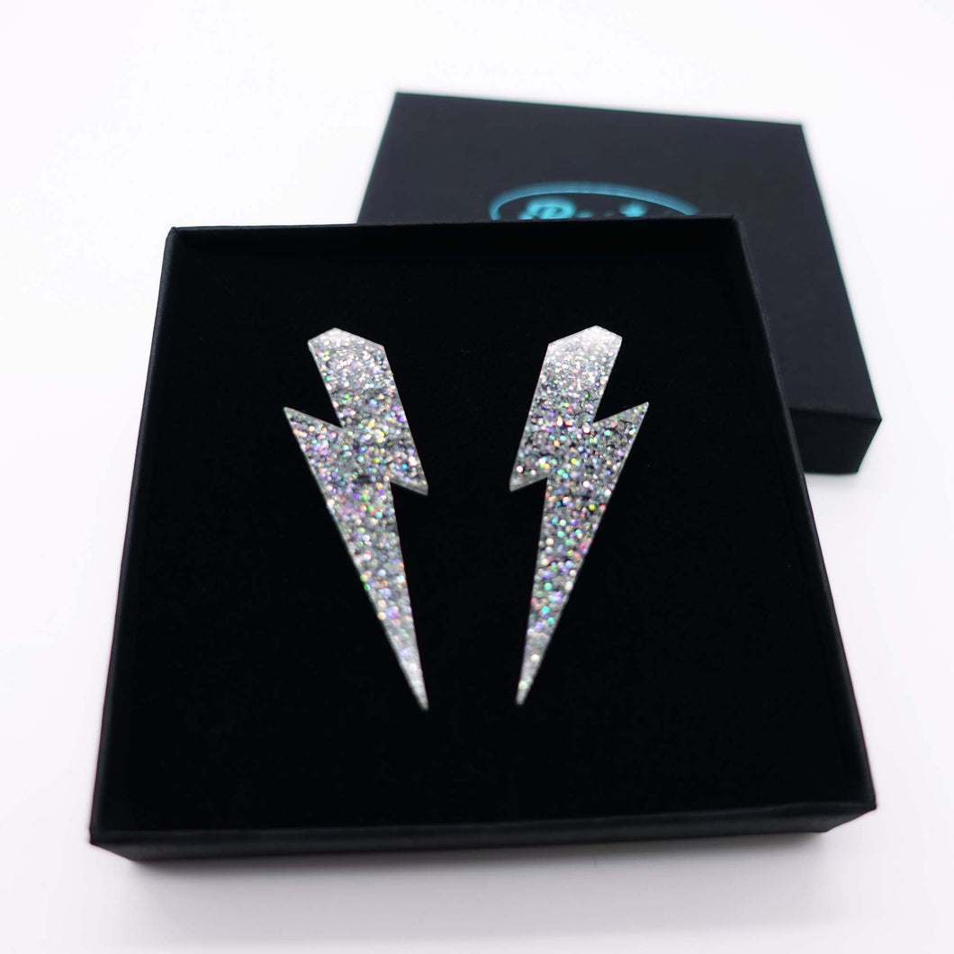 holographic silver large lightning bolt stud earrings shown in box
