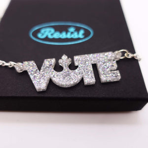 close up on box of holographic silver glitter  vote necklace
