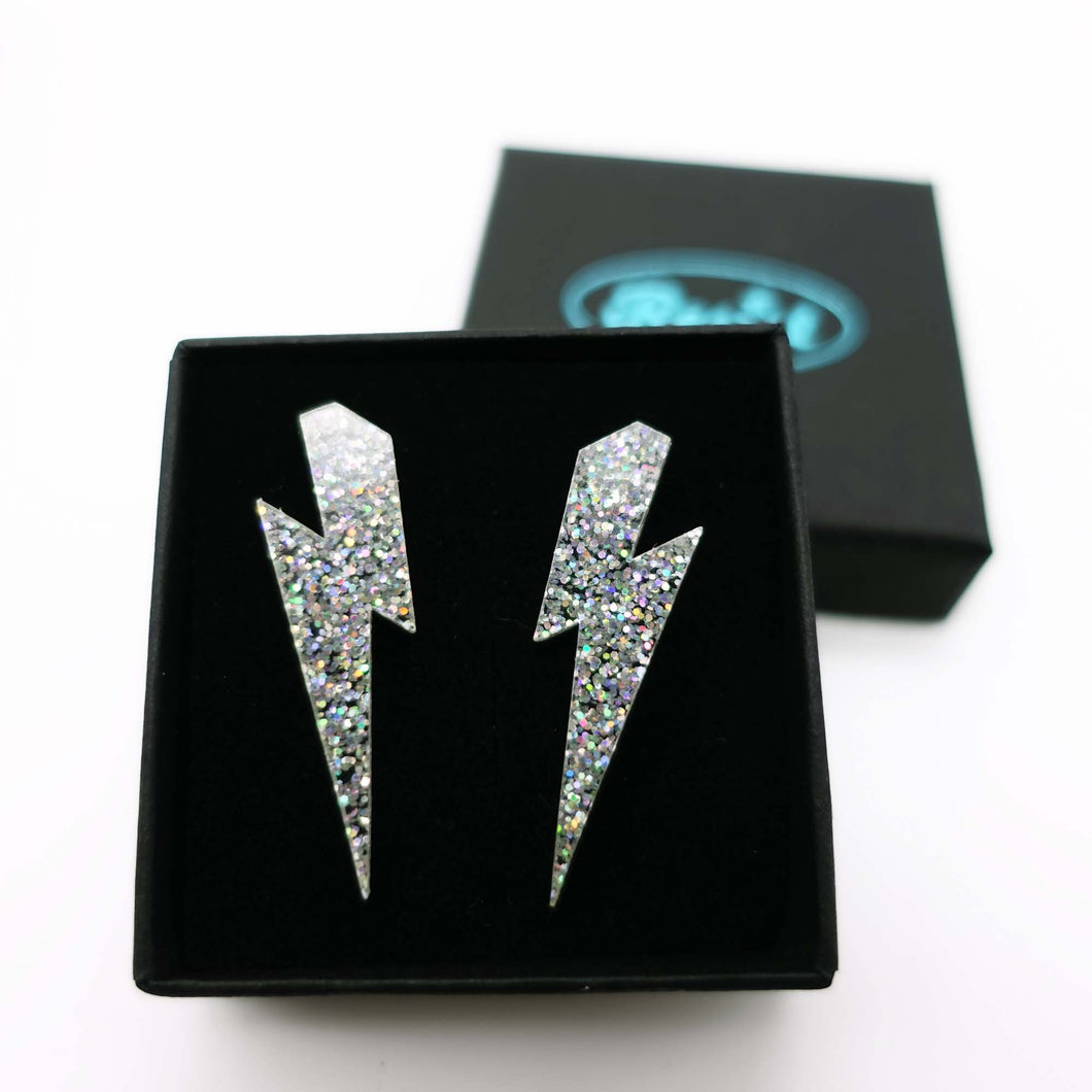 holo silver glitter medium lightning bolt stud earrings shown in box