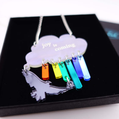 close up of joy is coming necklace in rainbow colours with bird