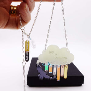 Joy is coming necklace in sunshower colours with Listen I love you tag, shown hanging from a hand