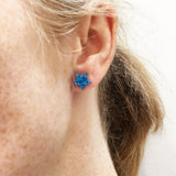 model wears blue glitter small star earrings