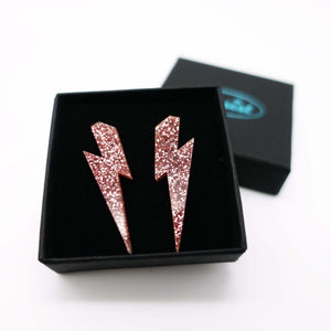 rose glitter medium lightning bolt stud earrings shown in box