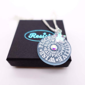 Close up of Pisces Zodiac Astrology necklace on box
