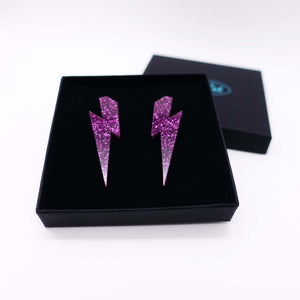 purple glitter  large lightning bolt stud earrings shown in box